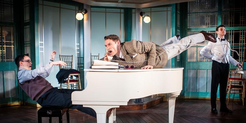 A man jumps across a grand piano to reach the telephone