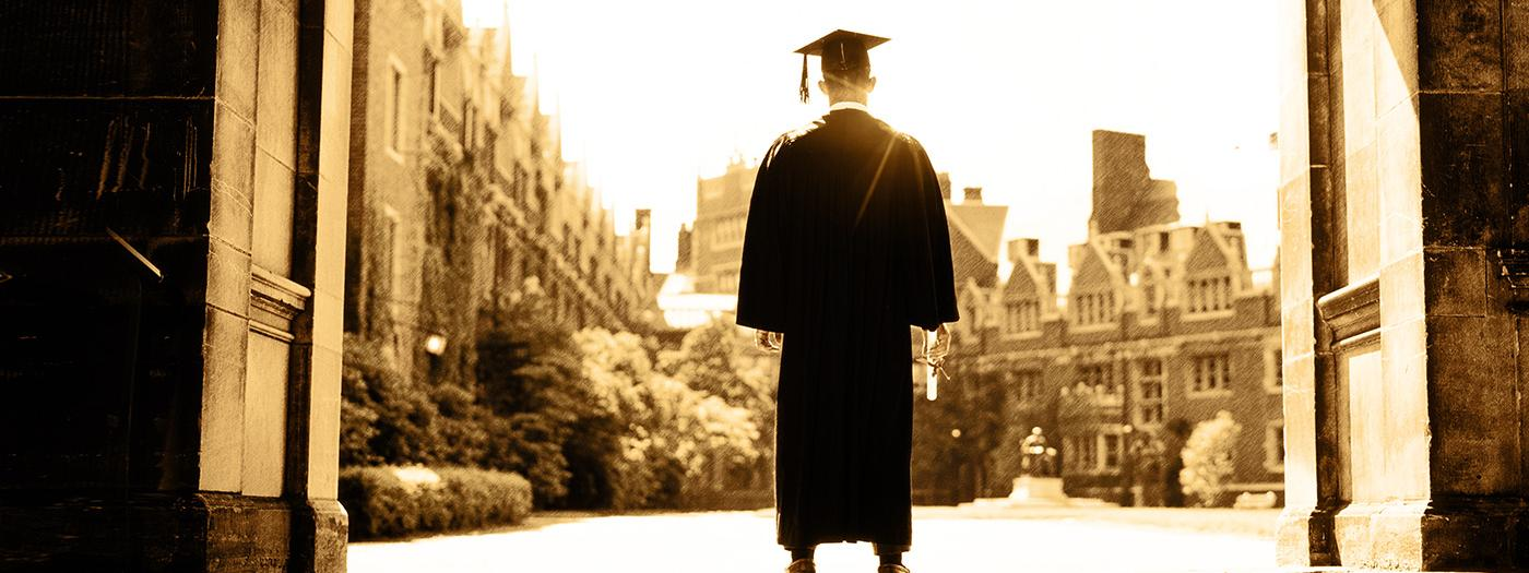 A boy in a cap and gown stands in front of a university college building