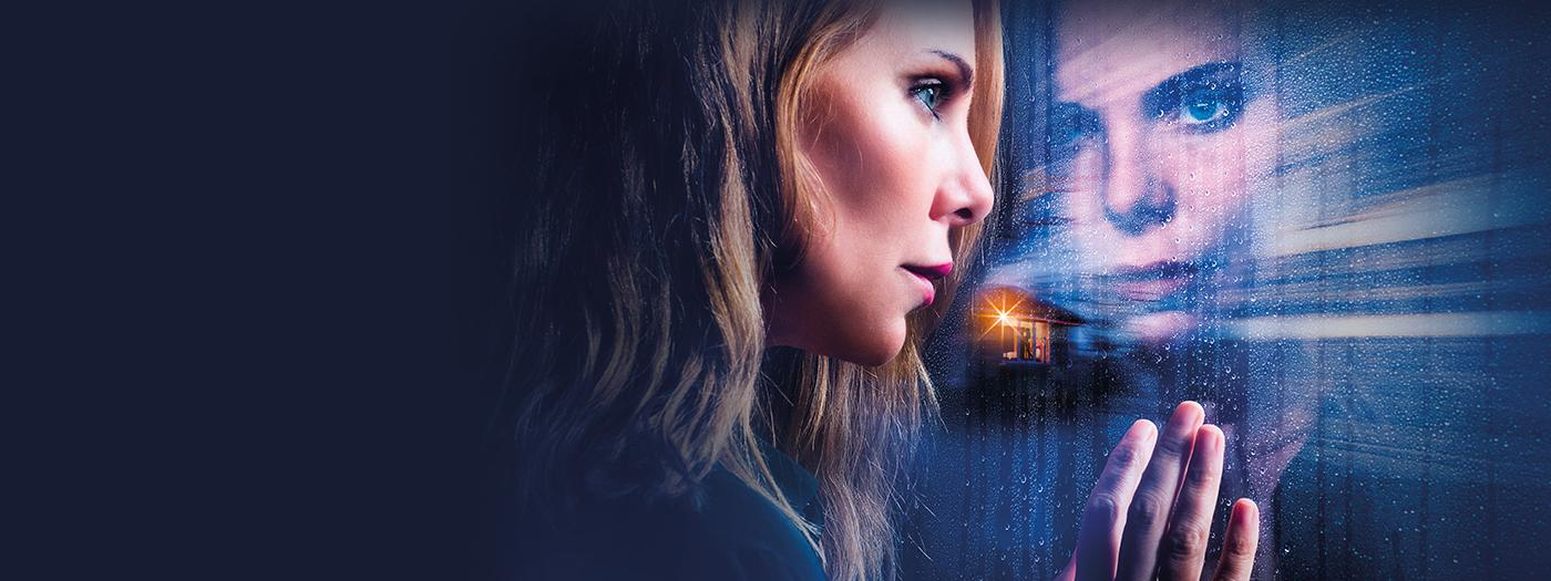 A woman stares out of a train window, there is a house with a yellow light on. You can see her reflection looking back.