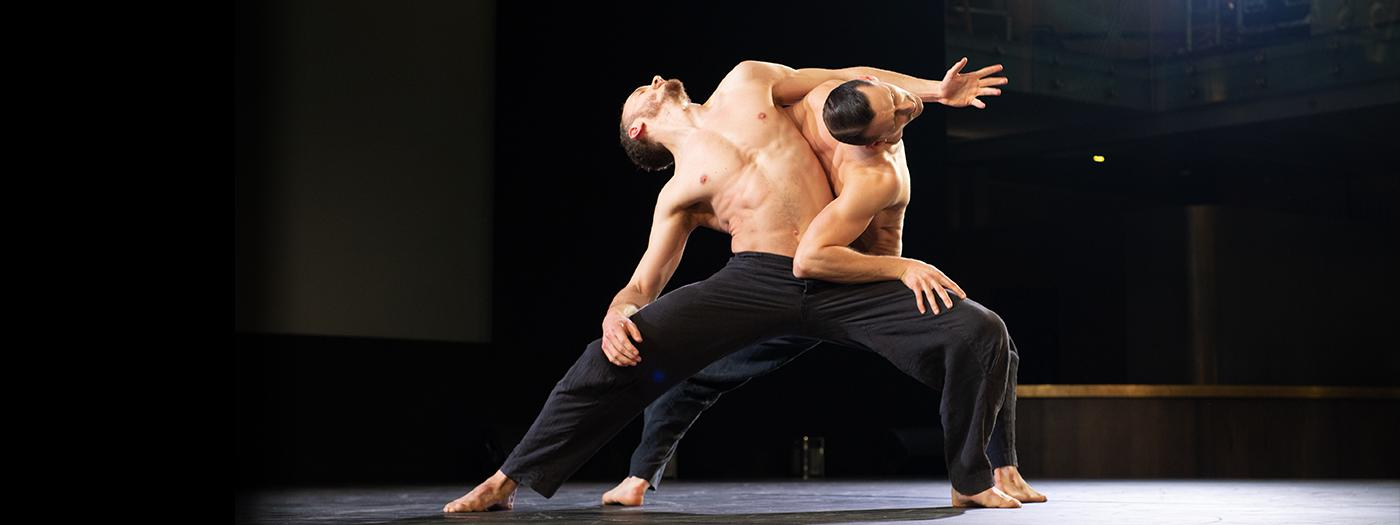 Two male dancers entwine on a bare stage