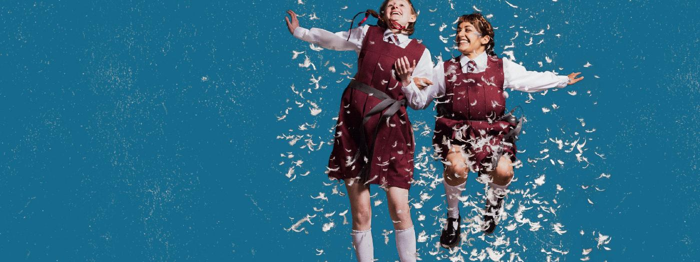 Two girls in school uniforms jump up in a cloud of feathers