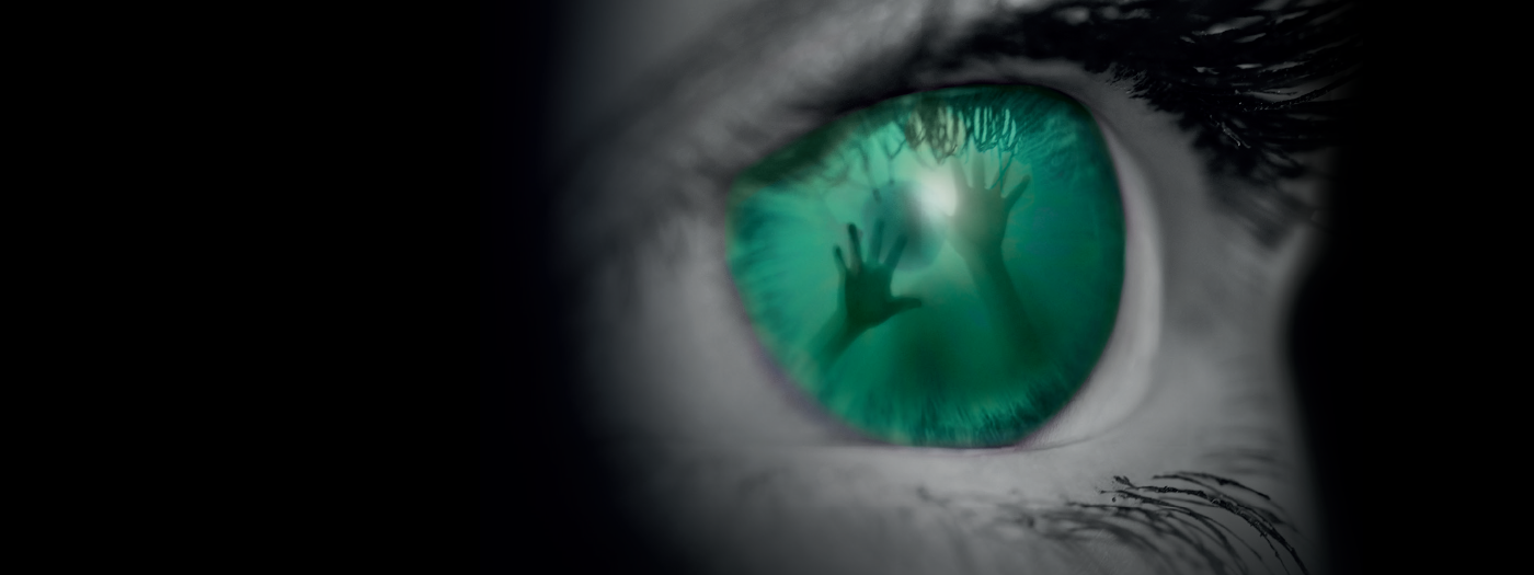 A close up of an eye, coloured vivid green with the image of someone trapped inside
